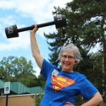 Staff member Mary Mitchell in front of the library holding up a set of weights.